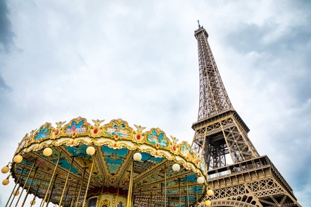 View from the bottom of The Eiffel Tower and Carousel in Paris in cloudy day in France