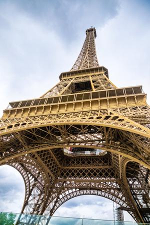 View from the bottom of The Eiffel Tower in Paris in cloudy day in France Stock Photo