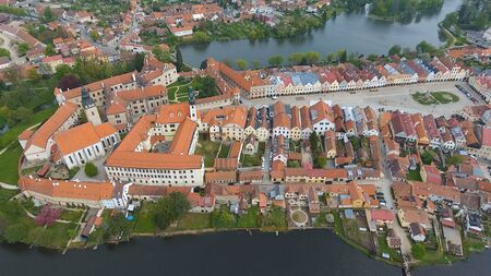 Aerial view of colorful buildings with red tile roofs at the medieval square and Old Castle in Telc in Czech Republic Banque d'images - 125335967