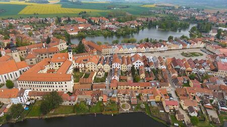 Aerial view of colorful buildings with red tile roofs at the medieval square and Old Castle in Telc in Czech Republic Banque d'images - 125335968