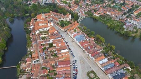 Aerial view of colorful buildings with red tile roofs at the medieval square and Old Castle in Telc in Czech Republic Banque d'images - 125335972