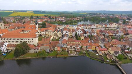 Aerial view of colorful buildings with red tile roofs at the medieval square and Old Castle in Telc in Czech Republic
