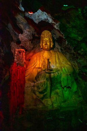 Beautiful illuminated multicolored Big Buddha in Danzhou Stone Flower Caves, Geopark next to Haikou in Hainan, China