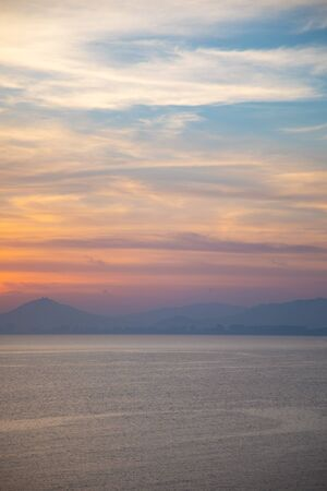 A peaceful scene of a calm ocean and gentle sunset, Asia