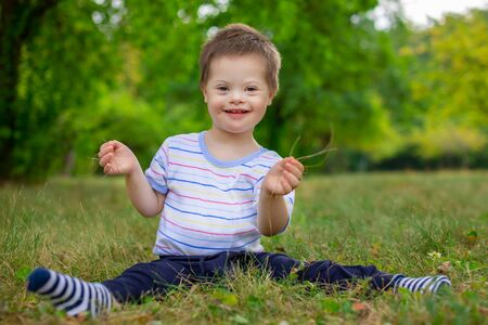 Portrait of Cute small boy with Down syndrome, child playing in summer day on nature Standard-Bild