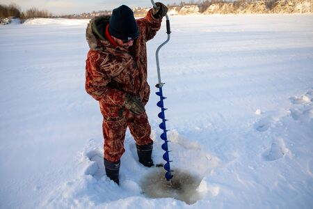 Kemerovo, Russia - 23.02.2019: A fisherman drills a hole in the ice to catch fish, Tom river in Kemerovo in Russia