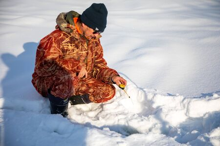 Kemerovo, Russia - 23.02.2019: A fisherman fishing in a hole in the ice to catch fish, Tom river in Kemerovo in Russia