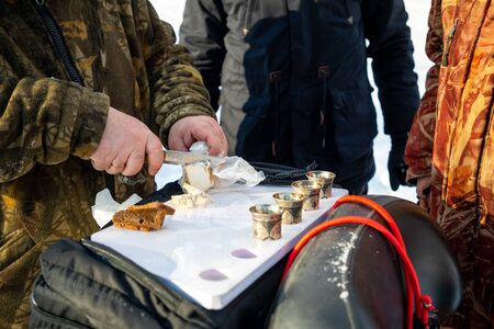 Kemerovo, Russia - 23.02.2019: Man cuts lard to drink vodka on nature during winter fishing in Siberia in Russia