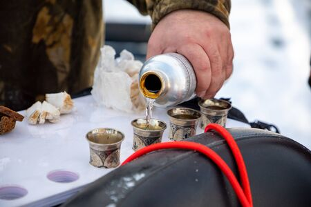 Man pours vodka on nature during winter fishing in Siberia in Russia