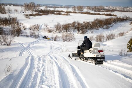 Rider on the snowmobile in nature of Siberia in Russia