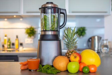 Making green smoothies with blenderat home in kitchen, healthy eating lifestyle concept 版權商用圖片