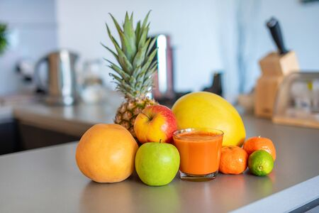 Different tropical fruits and smoothie on table on home kitchen background, healthy eating lifestyle concept