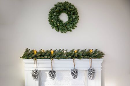 Fireplace with beautiful Christmas wreath, decorations in living room