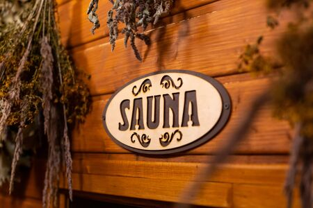 Dried herbs and branches on wooden background with inscription sauna 版權商用圖片