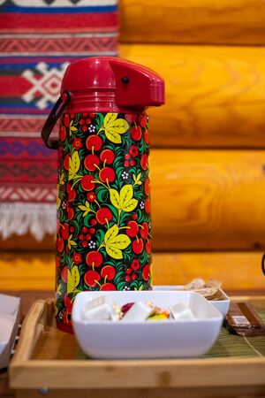Tea thermos in Russian folk Khokhloma style and candies on the table on wooden background 版權商用圖片
