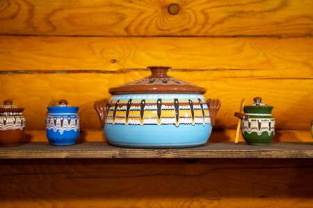 Old fashioned kitchen utensils in Russian folk style on wooden background