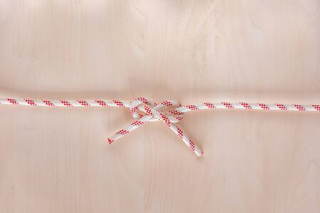 Carrick bend ship knot on wooden background, boating knot 版權商用圖片
