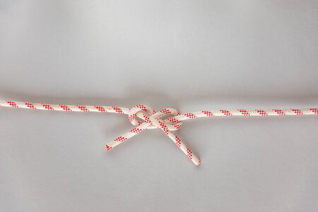 Carrick bend ship knot on grey background, boating knot Banco de Imagens - 140093942
