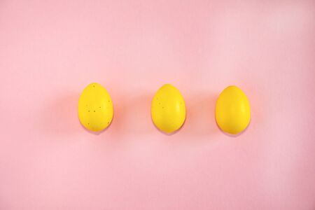 Yellow easter eggs on pink background with text copy space