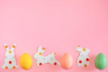 Colorful easter eggs and paper silhouettes of an easter bunnys on pink background with text copy space