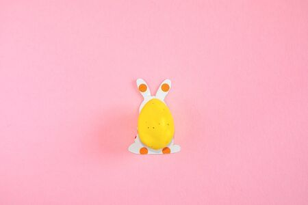 Easter egg and paper silhouettes of an easter bunny on pink background with text copy space