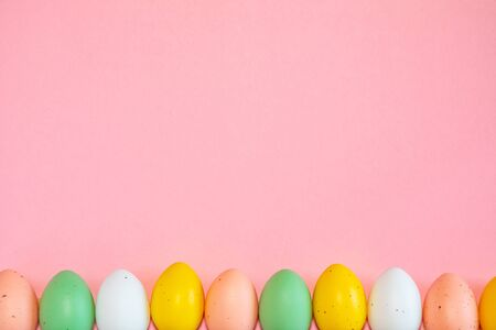 Colorful easter eggs on pink background with text copy space
