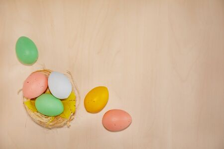 Colorful easter eggs on wooden background with text copy space