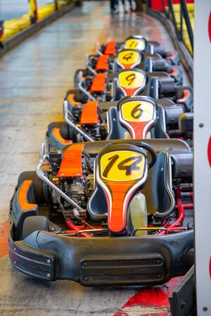 Row of carts with approval yellow numbers, ready to start inside a open track circuit, Prague, Czech Republic