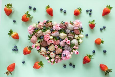 Heart shaped box with handmade colorful chocolate covered strawberries with different toppings and flowers as a present on Valentines day on green background