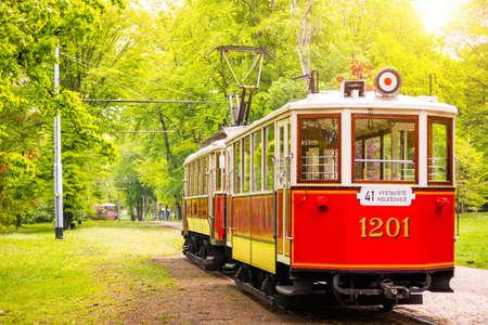 Prague, Czech Republic - 30.04.2019: Retro tram on green street in sunny spring day, Prague, Czech republic