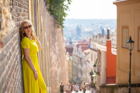 Young blonde woman exploring old town of Prague in sunny day in Czech republic