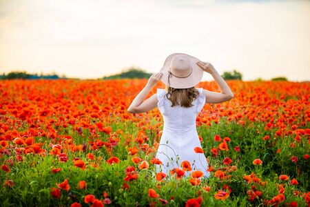 Woman with hat is standing in poppy field and enjoying a sunset in Czech republic