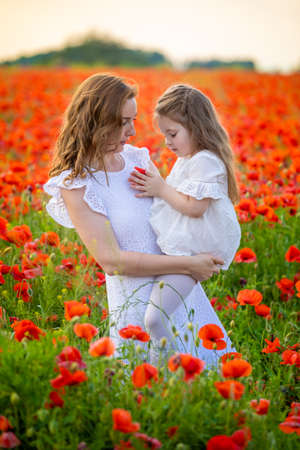 Beautiful mother and her daughter in spring poppy flower field in Czech republic Фото со стока