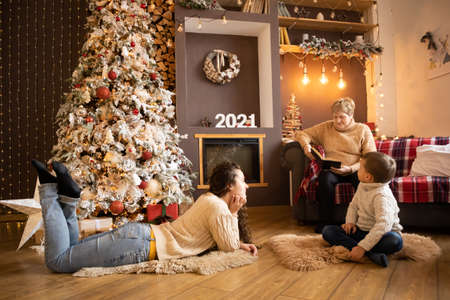 Grandmother reading book to grandchildren near Christmas tree at decorated home, Happy New year 2021 Banco de Imagens