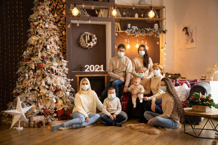 Multi Generation Family in protective face masksnear Christmas tree in modern decorated home, Happy New year 2021