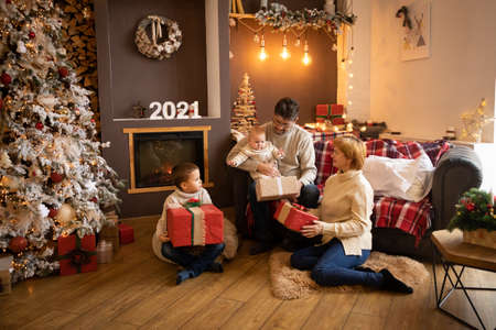 Family Opening Christmas Presents near Christmas tree in modern decorated home, Happy New year 2021