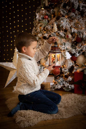 Little boy in holding a white lantern in his hand and sitting near the Christmas tree at home, Happy New year Banco de Imagens