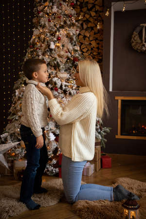 Mother and son are enjoying near christmas tree in modern decorated home, Happy New year