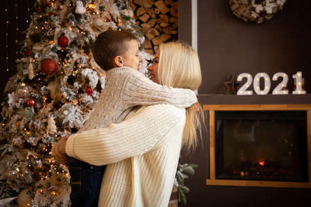 Mother and son are enjoying near christmas tree in modern decorated home, Happy New year 2021