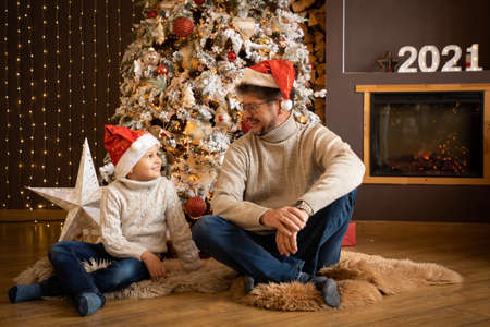 Father and son in christmas hats are enjoying near christmas tree in modern decorated home, Happy New year 2021 Banco de Imagens