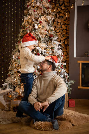Father and son in christmas hats are enjoying near christmas tree in modern decorated home, Happy New year