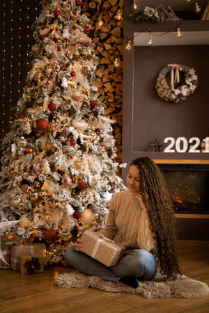 Girl in knit sweater sitting on the background of Christmas tree at home, Happy New Year 2021