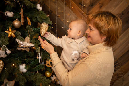 Beautiful happy mother with her ittle daughter in knit sweater decorating Christmas tree at home, Happy New year 2021