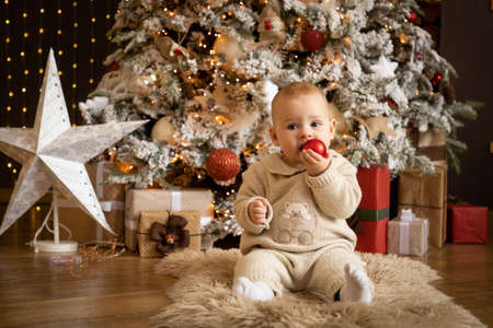 Cute baby girl sitting with Christmas Ball near Christmas trees at home, Happy New year