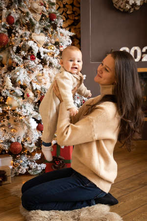 Beautiful happy mother with her ittle daughter in knit sweater sitting on the background of Christmas tree, Happy New Year 2021