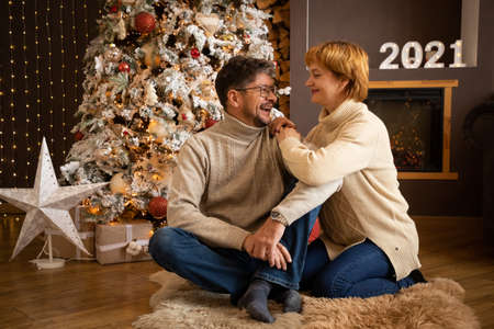Couple in knit sweater sitting on the background of Christmas tree at home, Happy New Year 2021