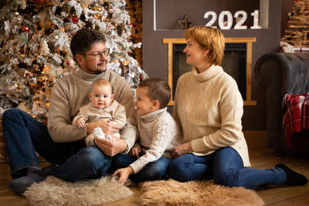 Family near Christmas tree in modern decorated home, Happy New year 2021 Banco de Imagens