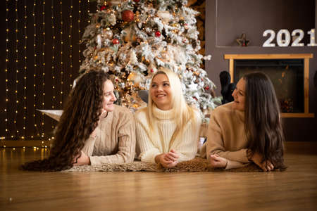 Three beautiful and cute girls lying near Christmas tree, dressed in warm clothes, smiling and waiting for Christmas holiday, Happy New Year 2021