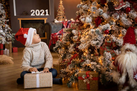 Little boy in holding a gift in his hand and sitting near the Christmas tree, Happy New year 2021