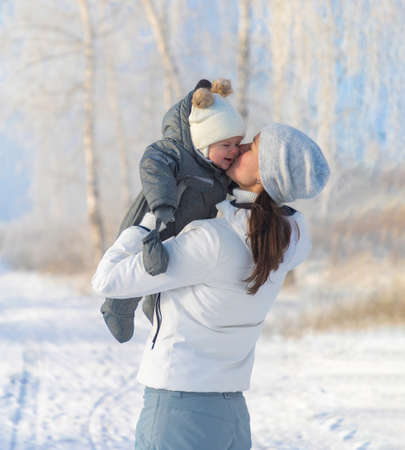 Happy mother and baby is playing on a winter nature walk in Siberia, Russia Banco de Imagens